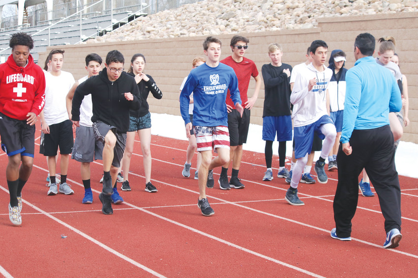 Coach Andy Cornell directs the warmup exercises for sprinters and hurdlers during the Feb. 28 Englewood High School track team practice. Cornell and Ryan Wyss are coaching the team this season for the first time and there are about 40 athletes are out for the team, including about 10 girls from St. Mary's Academy.