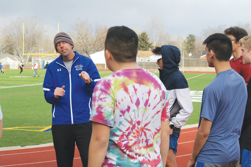 Englewood coach Ryan Wyss explains the route he wants his distance runners to follow during track team practice Feb. 28. Wyss said he was pleased with a turnout of about 40 athletes for his first season coaching track and field. He also coached Pirate cross country and he said he will primarily coach distance runners while Andy Cornell, who shares the head coaching duties, works with sprinters and hurdlers.