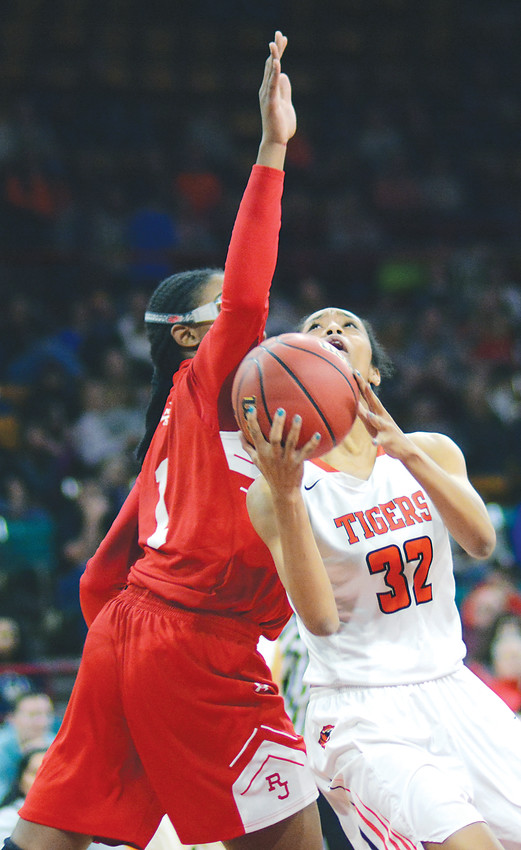 Lakewood senior Sassy Coleman (32) takes the ball up against Regis junior Francesca Belibi during the Class 5A state semifinal game March 8 at the Denver Coliseum. The Tigers finished their season with a 23-4 record after a 47-34 loss to the Raiders.