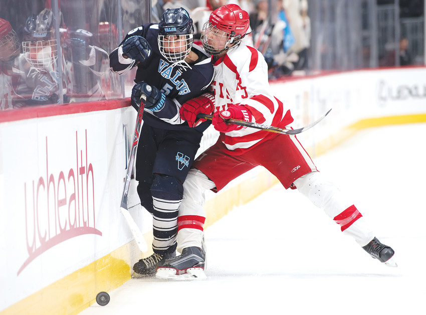 Regis Jesuit's Nolan Sargent, right, takes Valor Christian's Max Malinski to the boards as they both try to chase down the loose puck.  Regis ended up on top winning the state championship, 2-0, Tuesday night at the Pepsi Center.