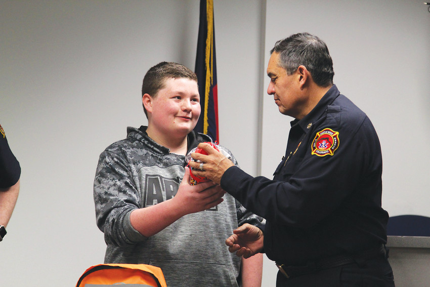 Zander Eaton accepts a gift from Castle Rock Fire Chief Art Morales following a presentation he gave at the Castle Rock Fire and Rescue headquarters about go bags and emergency preparedness.