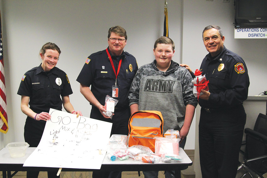 Fire and Life Safety Educator Colleen Sanderlin, Assistant Chief Craig Rollins and Fire Chief Art Morales stand with Zander Eaton following a presentation he gave about packing go bags with survival supplies for emergency situations.