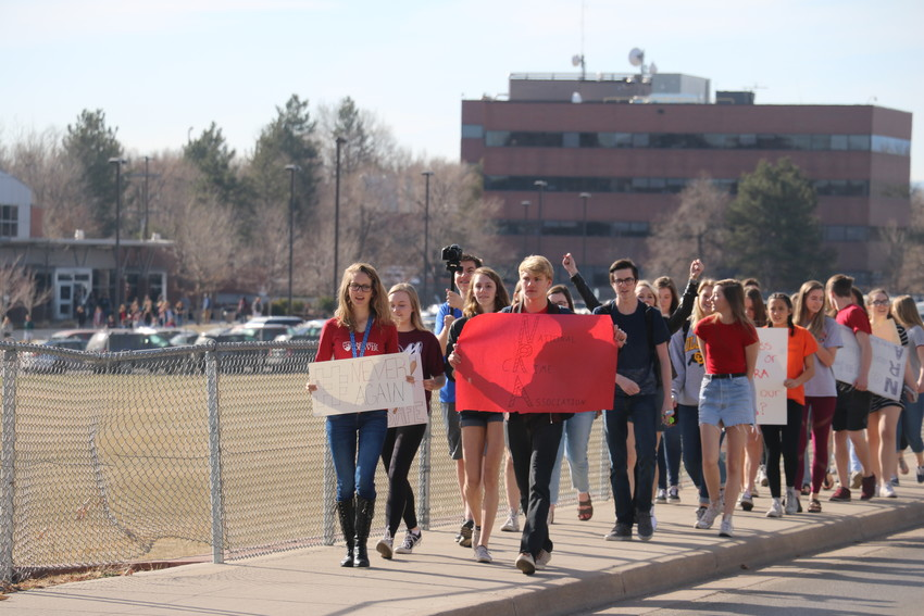 A stream of several hundred students leave Lakewood High School to stand along Kipling Street on March 14. The walk-out was one of many in the metro area to honor victims of gun violence.
