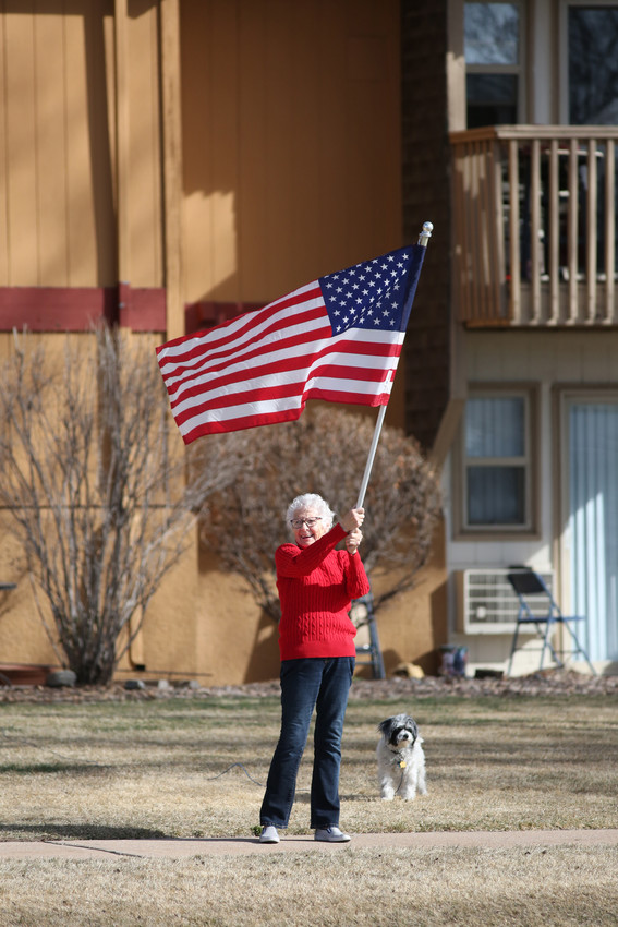 "Betty Campbell, 85, waves the American Flag across the street from where Arvada West students stood during their walkout protest. Campbell said she wanted to support the students. ""I'm old,"" she said. ""But that doesn't mean I don't want to be there next to the kids."""