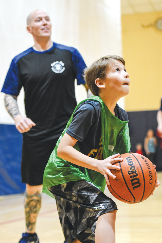 "Jacob Taylor,10, of Thornton, looks to get a shot off ahead of Northglenn Police Officer Nate Erwin, during a ""Kops vs. Kids"" basketball game March 9 at the Northglenn Recreation Center."