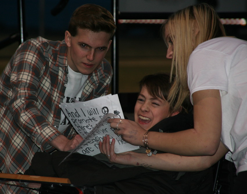 Sam Craig of Chatfield Senior High School, left, and Emmy Adams of Golden High School, right, assist Wheat Ridge High Schooler Jack Barnide, center, with his speech at the Jeffco Never Again Rally on March 14 at the North Area Athletic Complex. Barnide stated he would promote peace, and asked others to join him.