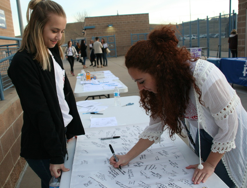Golden High Schooler Kate Bain, left, looks on as Dejah Watson, also a student at Golden High School, signs a banner on March 14 at the Jeffco Never Again Rally. The banner will be sent to Marjory Stoneman Douglas High School in Parkland, Florida.