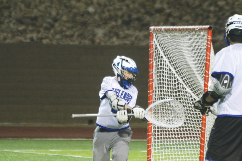 Englewood goalie Riley Graves, 4, deflects a shot during the Pirates' March 9 lacrosse season opener against a talented Golden team. Graves, playing his first game in goal, made a number of deflections and saves but the Demons fired shot after shot on goal and won the game, 19-2.