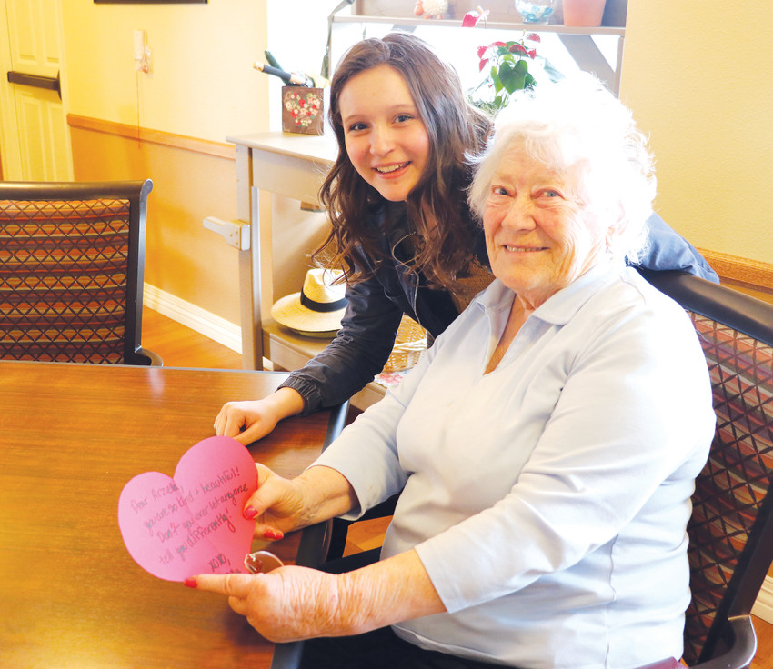 "Ally Atkins, left, exchanges a heartfelt note with Arzella Dirksen, a resident of Brookdale Highlands Ranch, a community that offers memory care for seniors. ""The people are so nice, so kind and so willing to be open,"" said Atkins, 13."