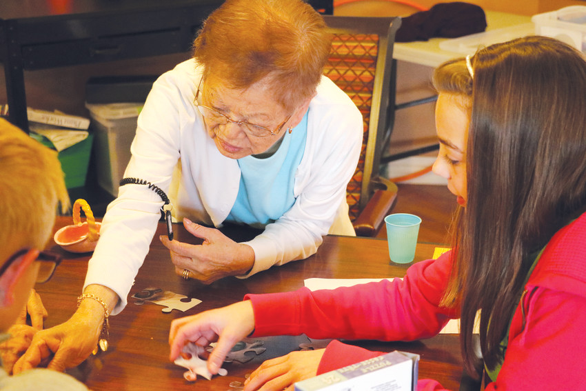 Brookdale resident Kaz Denkenbeiger, left, makes a puzzle with Edie Cingrani, a student at Mountain Ridge Middle School. The two came together because of Bessie's Hope, a program that coordinates volunteers with seniors in assisted living centers.