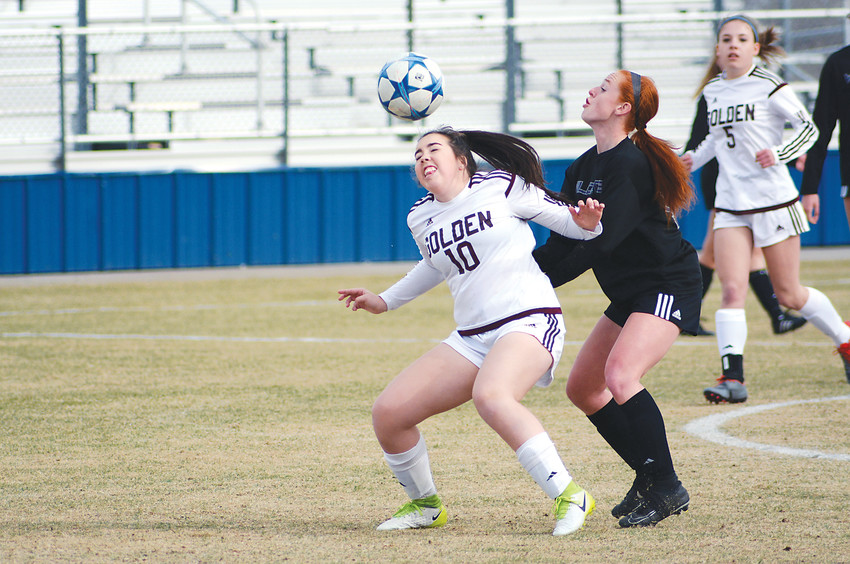 Golden freshman Lily Fell (10) gets her head on the ball in front of Arvada West junior Makenna Fowler on March 14 at the North Area Athletic Complex. The Wildcats edged the Demons, 2-1.