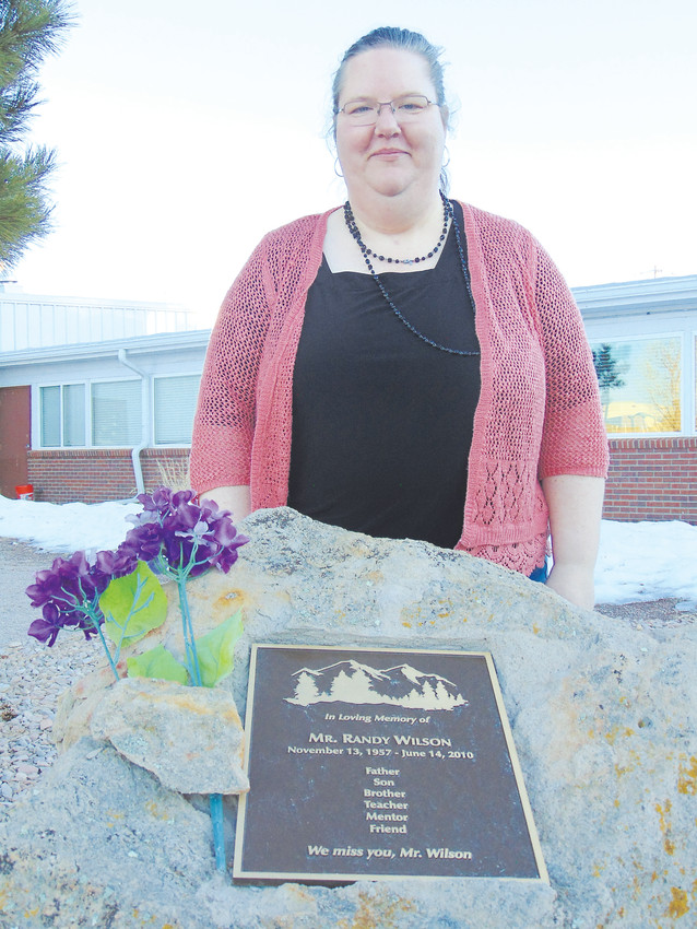 Kiowa school counselor Liz Morrone stands behind a plaque remembering teacher Randy Wilson, who was found dead in 2010.