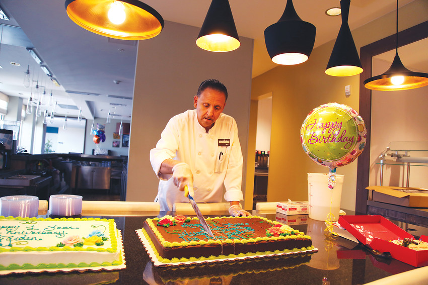 Jamie Rios, executive chef at the Hilton Garden Inn Arvada, cuts cake to share with the community on the hotel's first birthday.