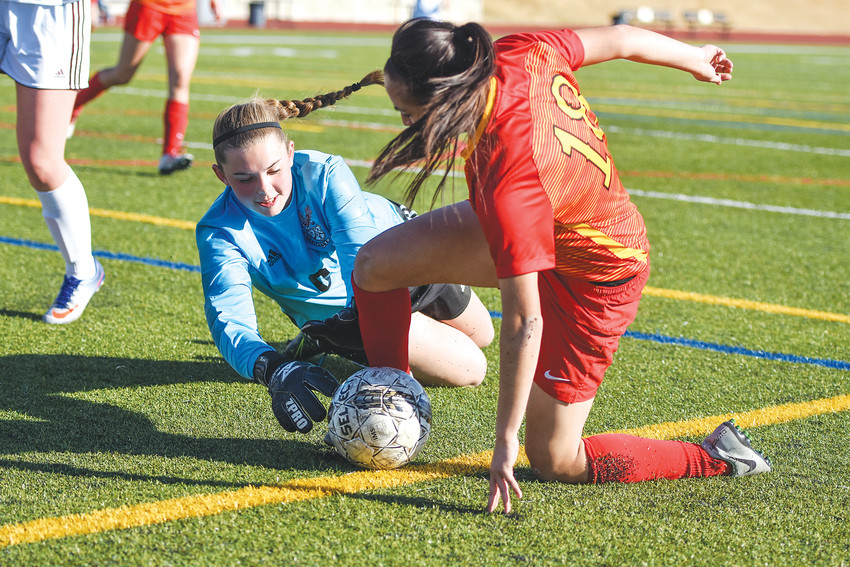 Horizon goalkeeper Bailey Flanigan, left, attempts to secure the ball from Northglenn's Samantha Dominguez Reyes, in late first-half action March 13, 2018 at District 12 North Stadium in Westminster. The Hawks edged the Norse, 4-3.