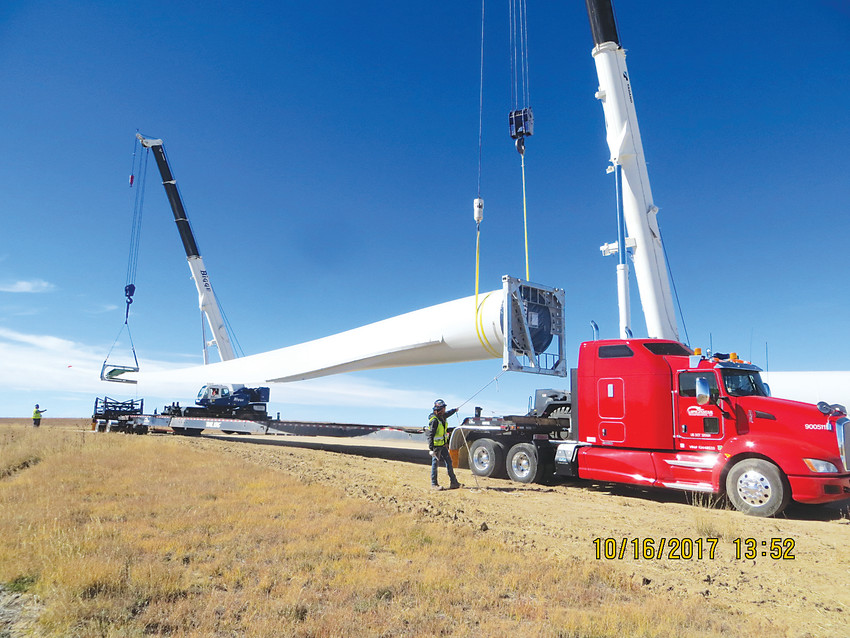 Workers unload a turbine blade at Rush Creek Wind Farm. Running through eastern Elbert County, construction just ended on the foundations and turbine assembly recently began.