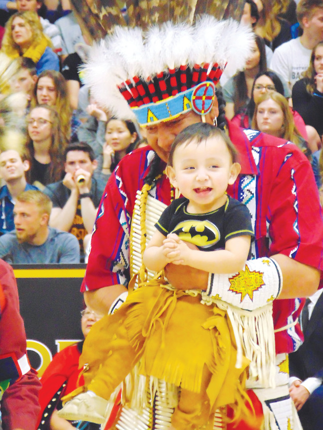 Annin Soldier Wolf holds his son Roger, 1, while the two dance in Arapahoe High School's gym.
