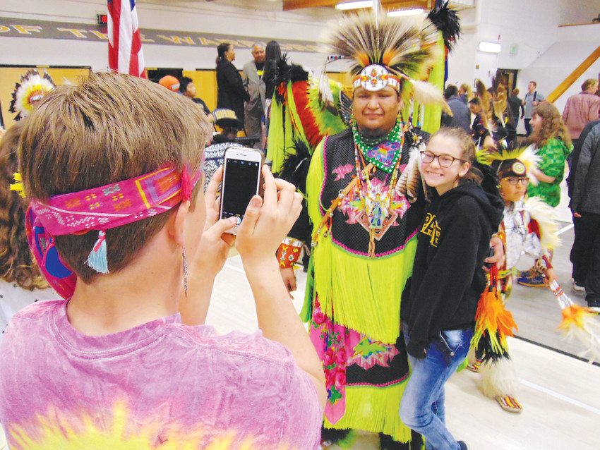 Arapahoe High School freshman  Beth Killinen poses for a photo with Arapaho dancer Dean Littleshield.