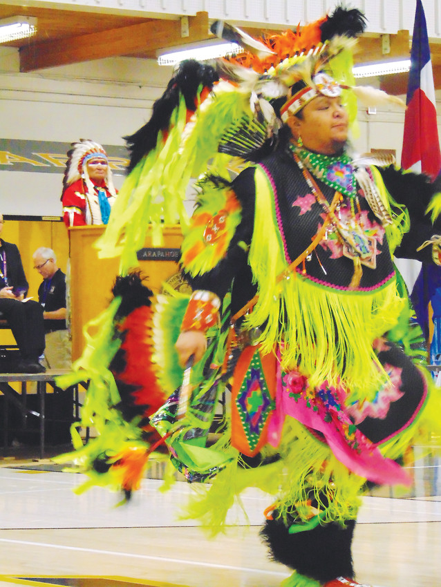 Dean Littleshield dances in a traditional ceremonial costume while tribal elder Darrell Lone Bear, left, looks on.