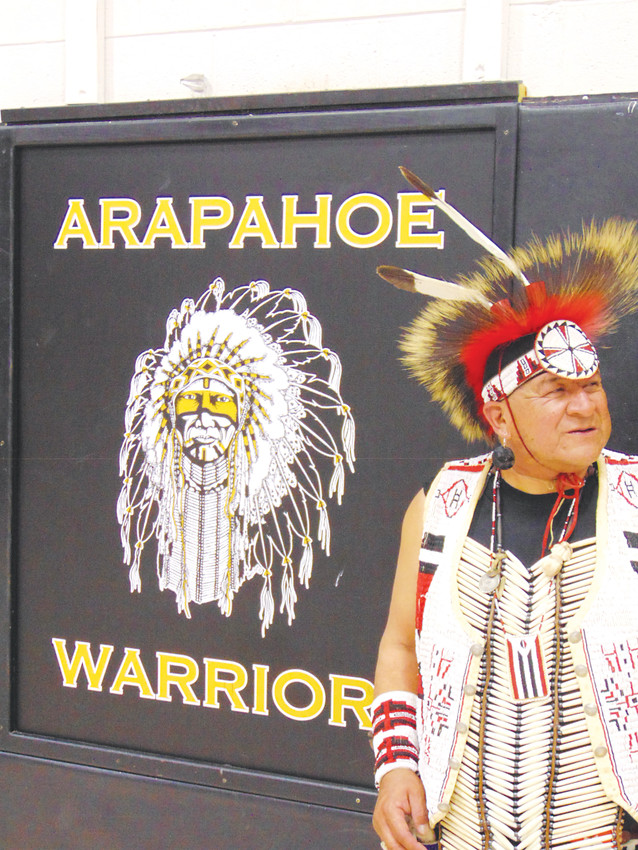 Lawrence Bell stands beside a painting of Arapahoe High School's Warrior mascot, which was painted by an Arapaho artist.