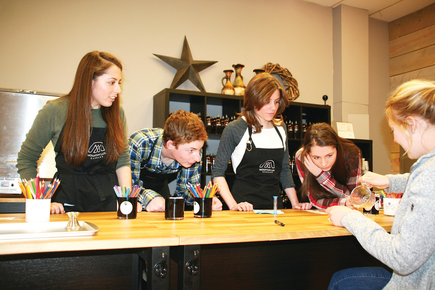The Molnar quadruplets, from left, Abby, Luke, Rachael and Julia, work with a customer on March 21 to make a custom-fragranced wax tart at Mountain Lux Candles in downtown Golden.