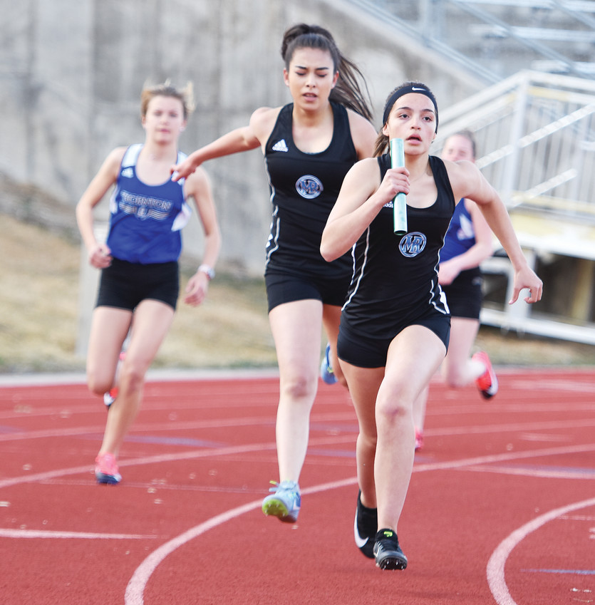 Right: Mountain Range freshman Ainsley Urquidi-Almonte, right, begins her leg of the girls 4 x 800-meter relay, after a handoff from teammate Jazmine Cerezo, during the Five Star Championships track & field meet March 21 at District 12 North Stadium in Westminster.