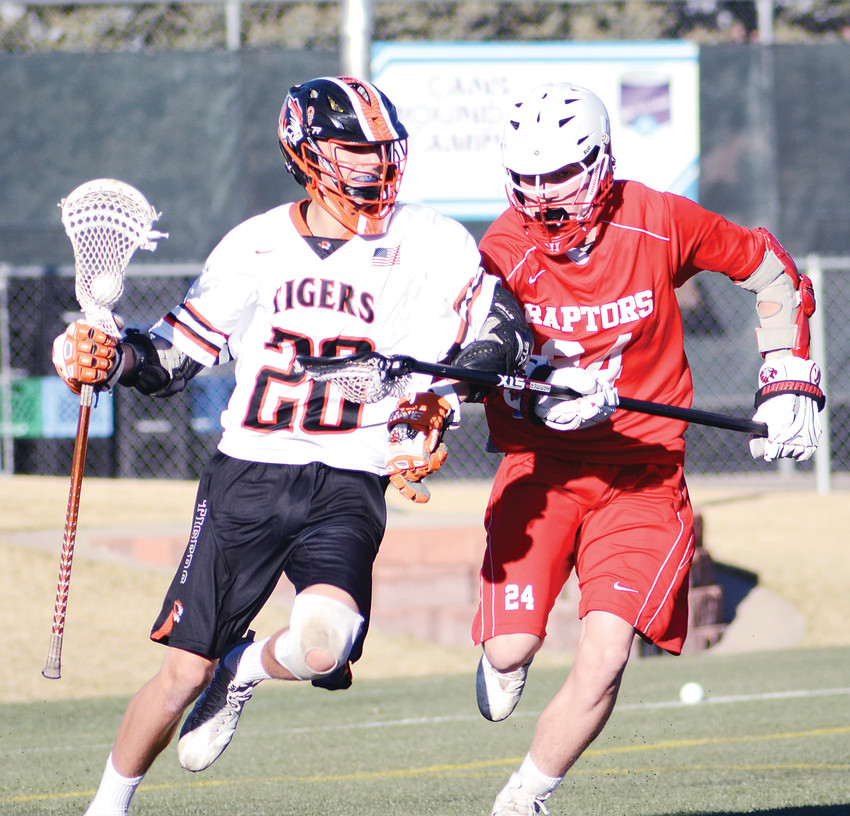 Lakewood's Evan Woods (20) fends off Eaglecrest freshman Ben Christ during the first quarter March 23 at Trailblazer Stadium in Lakewood. Woods scored five goals.