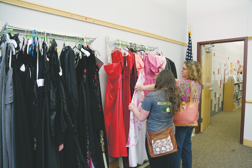Claire Frazier, 16, looks through potential prom dresses with her mom, Shari, at the Arvada Library March 31 during the prom swap.