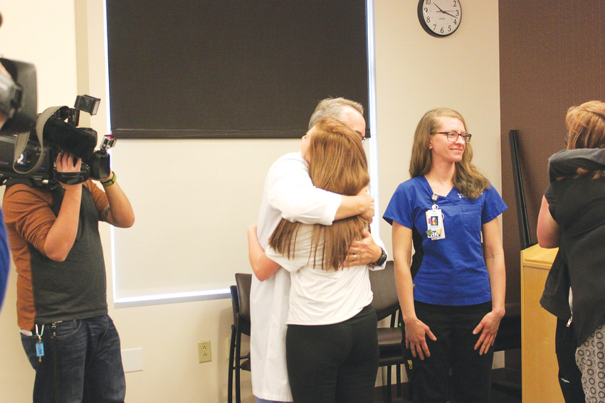 Morgan Koetter embraces Dr. Chris Winter, a trauma surgeon at Parker Adventist Hospital, who saved her life after a near-fatal car accident Dec. 17, 2017.