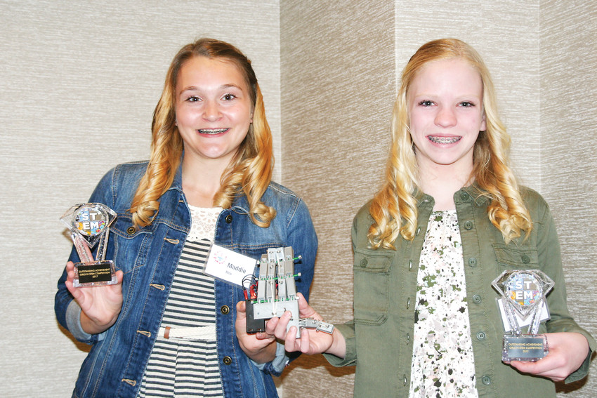 Maddie Rice, left, and Sophia Eakes, both middle schoolers at Bell Middle School in Golden, hold up their awards and bionic hand on International Women's Day, March 8, 2017, after winning first place in the Jefferson County Public Library's Girls in STEM Competition.