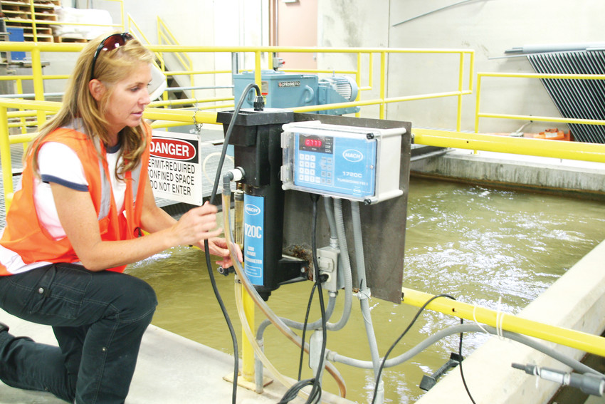Wendy Weiman, the project engineer for North Table Mountain Water and Sanitation District, checks the water clarity at the organization's water treatment plant near Highway 93 and West 64th Parkway in Golden.