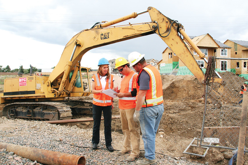 Wendy Weiman, left, the project engineer for North Table Mountain Water and Sanitation District, talks with, from left, laborer Olu Villalobos and foreman Fredy Peraza on a project where the crew was putting in pipe casing for a new development at McIntire Place in Golden.