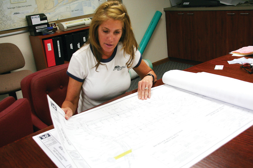 Wendy Weiman, the project engineer for North Table Mountain Water and Sanitation District, looks through water and sewer construction plans for a project she's working on at her office in Golden.
