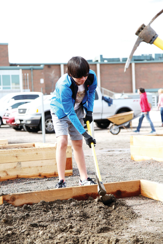 North Arvada Middle School eighth-grader Raiden Alford helps to break up dirt for a garden plot at the March 28 work day.