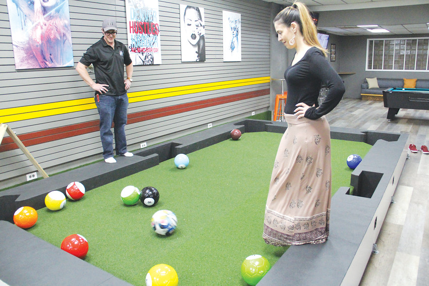 Vincenza Licata, right, takes a shot at the life-sized soccer-pool game called gamböl at Duffer Haus April 4, as owner Brian Meadows watches. Licata handles marketing for the bar.