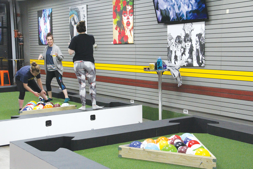 A group of friends sets up to play a life-sized soccer-pool combination game April 4 at Duffer Haus, a new bar on South Broadway in Englewood's downtown. The bar opened March 31.