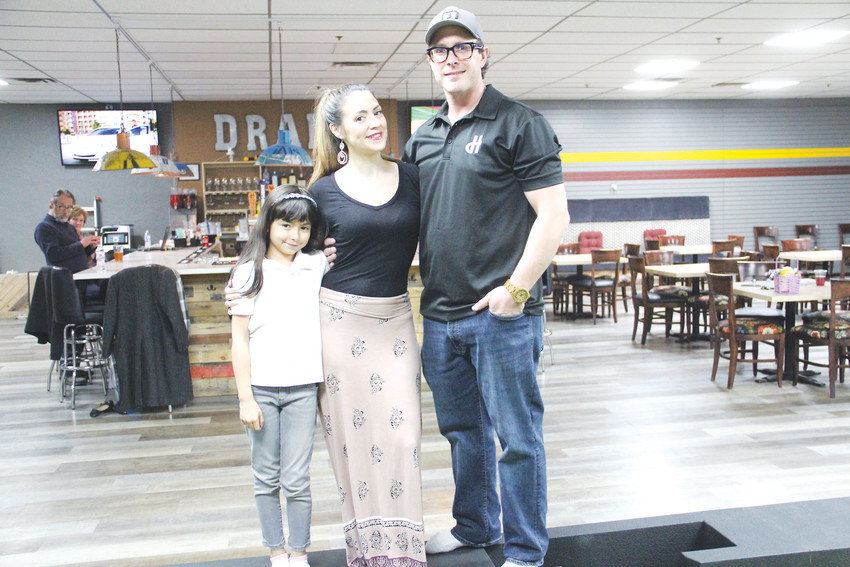 Right to left, owner Brian Meadows, marketer Vincenza Licata and her daughter, Valentina Licata, 8, at Duffer Haus on April 4. The bar is one of several new businesses in the Englewood downtown area.
