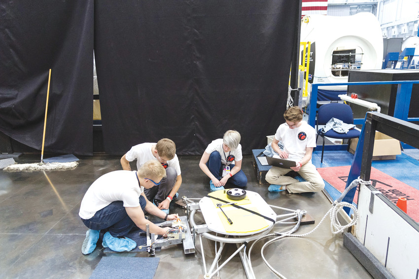 Warren Tech team members Aidan McTague, Javan Sandt, Zoe Maxwell and Mitchell Bowen work to rebuild their satellite launcher during the event at Johnson Space Center in Houston.
