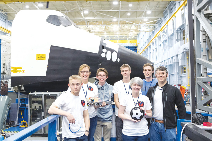 The team from Warren Tech poses with their project, teacher and NASA representatives in front of a mockup of the space shuttle cockpit.