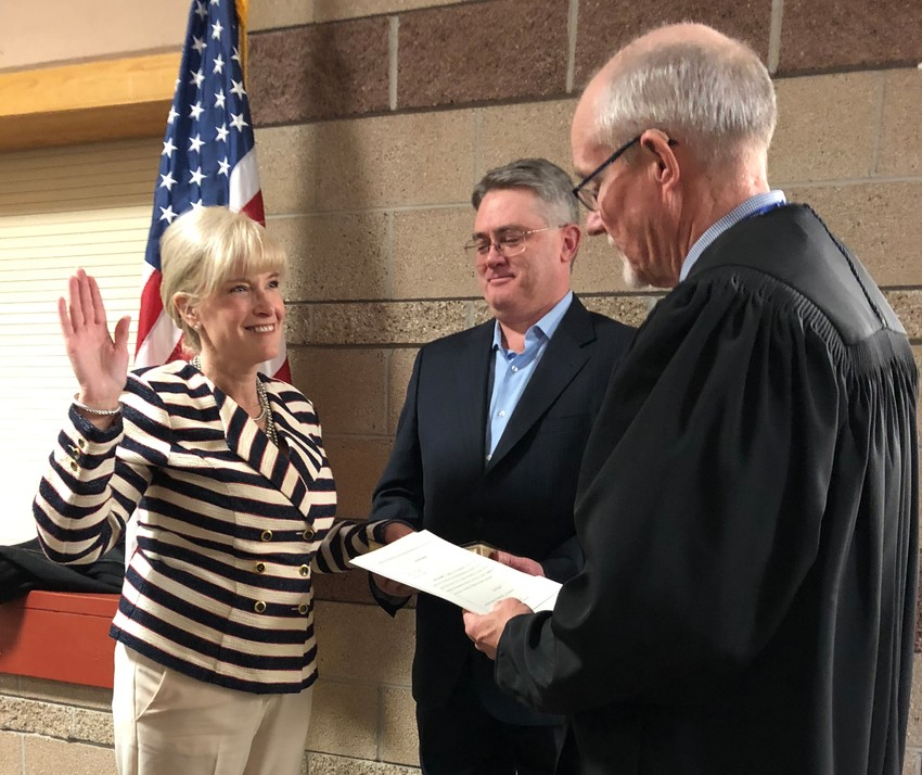 Diane Holbert is sworn in as the District 1 Douglas County commissioner on April 9 after being chosen to fill a vacancy left by David Weaver. Her husband, Chris Holbert, a state senator, is in the center of the photo.