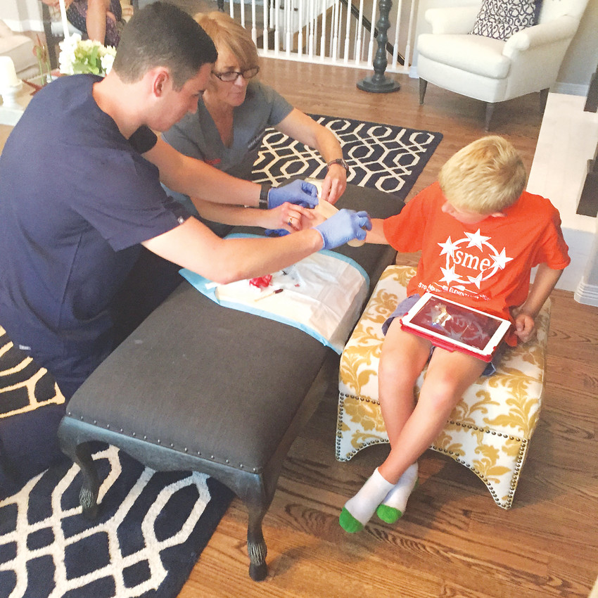A physician and EMT from DispatchHealth help Leigh Picchetti's 6-year-old son, who had an infected scrape on his thumb from a tumble on the trampoline. Completed in the home, the treatment took about four or five minutes.