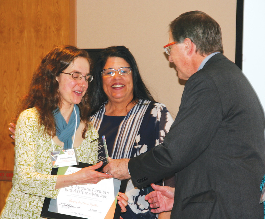 Rosalind May, left, the manager of the Four Seasons Farmers and Artisans Market in Wheat Ridge, accepts her public health champion award from Dr. Mark B. Johnson, the executive director of Jefferson County Public Health, right, and Jefferson County Commissioner Tina Francone, center.  The 2017 Public Health Champions of the Year awards ceremony took place on April 4.