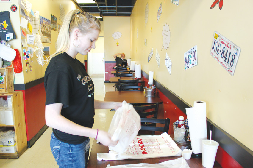 Reiley Sabo, 17, prepares bags for take out orders at The Chicken Shack in Parker. Sabo took her first job when she was 14 and is saving her paychecks to move into her own apartment.