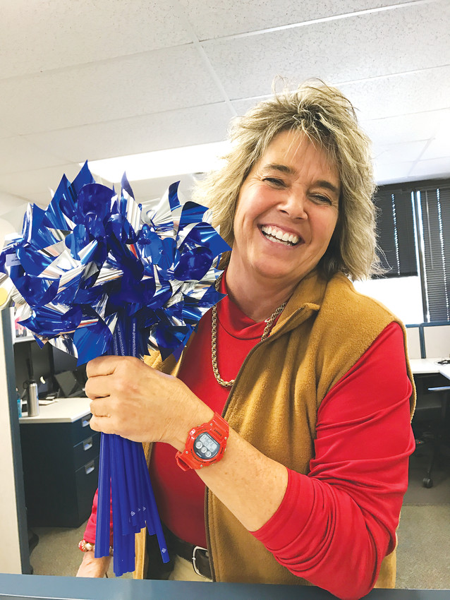 Detective Cheri Ells with the Wheat Ridge Police Department holds up some of the purple pinwheels that the department has put on display to help raise awareness about Child Abuse Prevention Month.