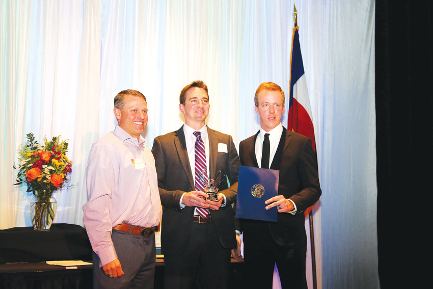 Michael McCarron and Andrew Heesaker present James Johnson (center) with an AYP Leadership Award.