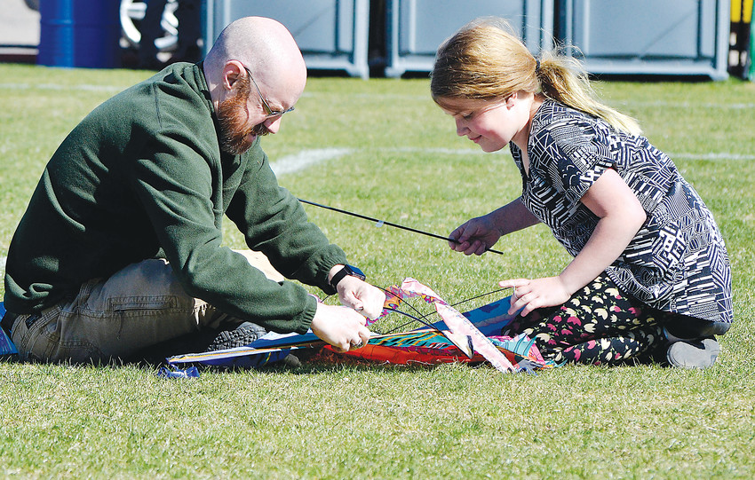 Darrell and his daughter, Sophie, 11, Brogdon of Arvada put together a kite at the annual festival.