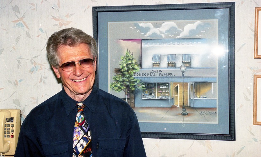 Del Miller smiles for a picture of himself with a drawing of Del's Tonsorial Parlor and Barbershop in 2006. Miller had a 49-year career as a barber in Golden.