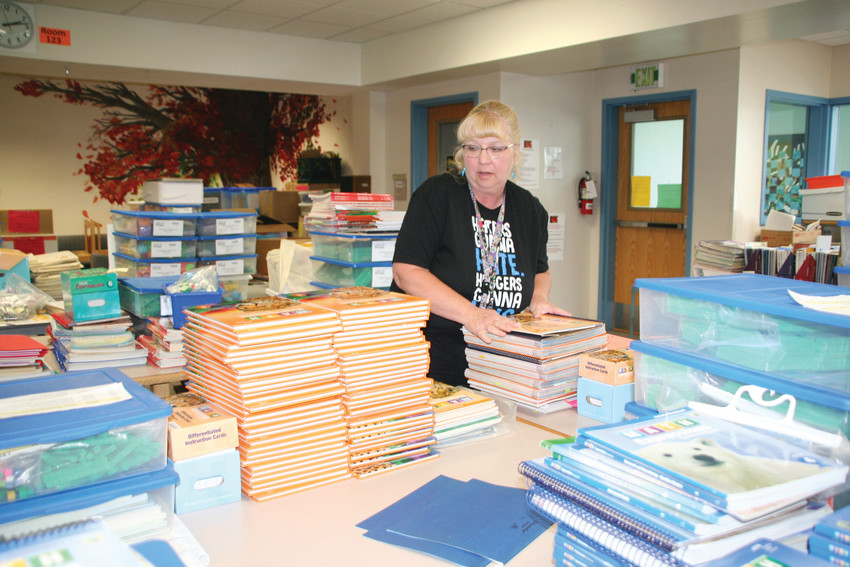 Pleasant View Elementary's librarian and special education para Sherrie Durfey organizes textbooks on May 23, 2017 — the last day of school. All of the school's materials and furniture were reallocated throughout the school district.