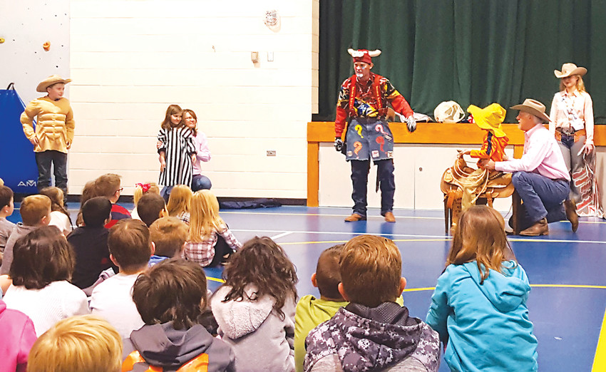 Elizabeth Stampede rodeo clown J.W. Winklepleck pretends to be a calf for the kids to catch at a Stampede to Read assembly.