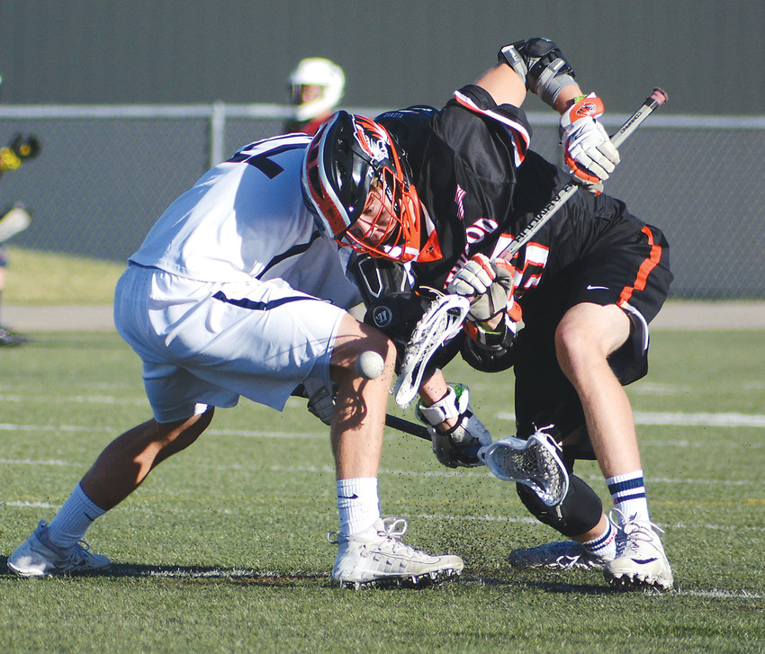 Lakewood freshman Nolan Hoefner, right, tries to win a face-off during the Tigers' conference showdown with Dakota Ridge on April 11 at Trailblazer Stadium. Lakewood suffered a 13-11 loss.