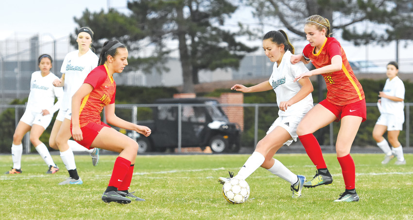 Westminster's Savannah Garcia, center, tries to control the ball between Northglenn's Lauren Woodhull, left, and Madison Hoy, right, during first-half action April 10 at Memorial Stadium in Westminster. The Norse defeated the Lady Wolves, 3-1.